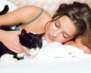 Young woman lying in bed stroking cat, close-up